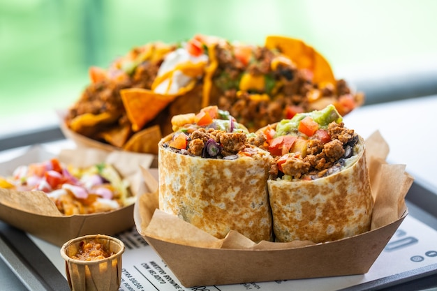 Mexican traditional food in a fast food cafe. salsa nachos and burrito with minced meat and guacamole
