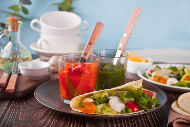メキシカン ビーガン トルティーヤ ラップ フラット ブレッドに野菜とソースのディップをディナー テーブルに