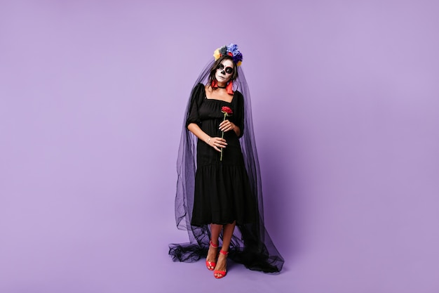 멕시코 미망인은 슬프게도 빨간 장미를 들고 있습니다. 신부 베일과 검은 옷을 입은 여자의 전신 사진.