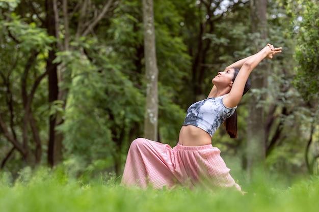 Мексиканская женщина занимается йогой в разных позах в открытом парке с травой и деревьями