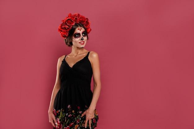 Мексиканская женщина в платье танцует на национальном празднике санта-муэрте в маске в форме черепа