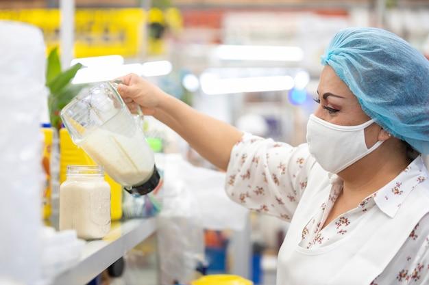 멕시코의 인기있는 시장에서 유리에 주스를 제공하는 멕시코 여성, 코로나 바이러스 전염병으로 인한 안면 마스크 및 d 대처