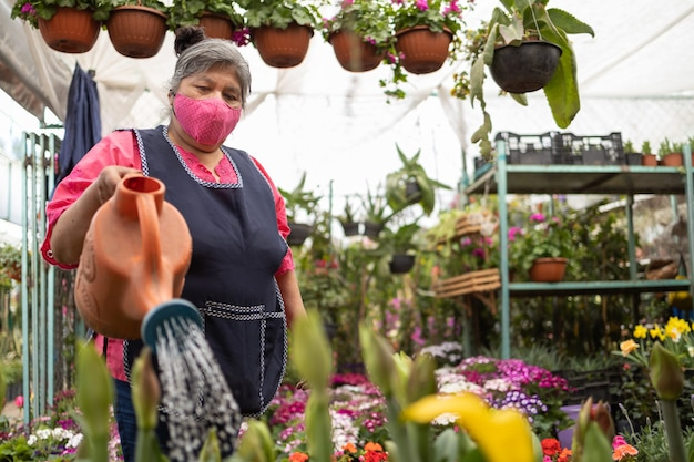 Mexican woman watering plants in nursery xochimilco, mexico, wearing face mask, new normal