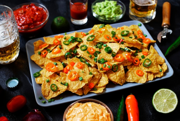 Mexican yellow corn tortilla chips nachos with jalapeno, guacamole, cheese sauce and salsa