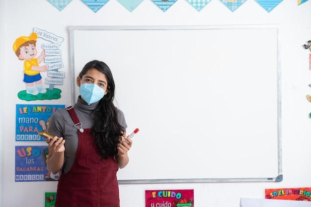 コロナウイルスのパンデミック後、学校に戻ってフェイスマスクを身に着けているメキシコの若い学校の先生