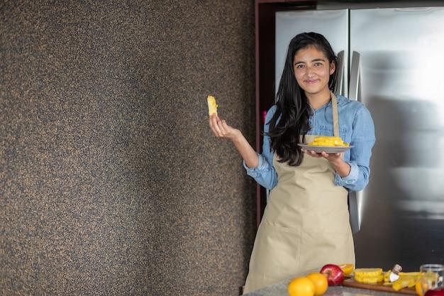 Мексиканская молодая женщина с ананасовым завтраком на кухне