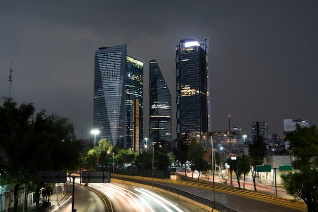 雨の日のメキシコシティの建物と、車からの光が一掃する下部の大通り