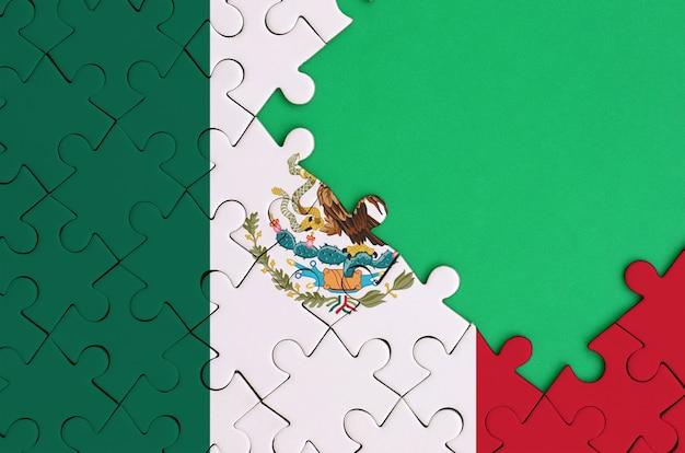 멕시코 국기는 오른쪽에 무료 녹색 복사 공간이있는 완성 된 직소 퍼즐에 그려져 있습니다.