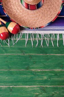 Mexico mexican sombrero maracas fiesta wood background vertical