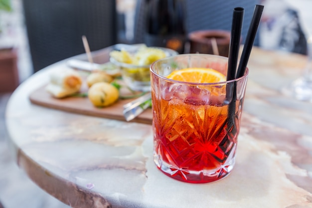 Mezcal negroni cocktail italian aperitivo on the table in the open area of restaurant