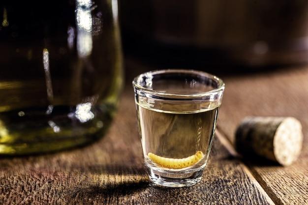 メスカル(またはメスカル)は一般に「幼虫のいるメキシコのテキーラ」として知られており、瓶の底にグサノ昆虫の幼虫がいます。幻覚剤と媚薬の特性を備えた飲み物。 Premium写真