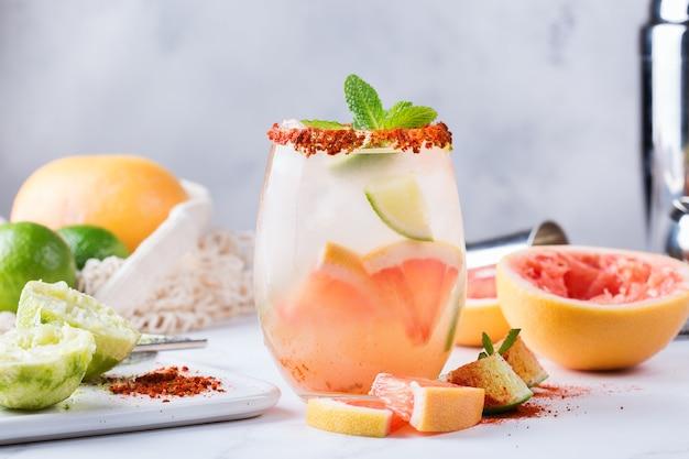 ガラスにグレープフルーツ、セルツァー水、チャイルドライムソルトリムを入れたメスカルまたはメスカルのパロマカクテル