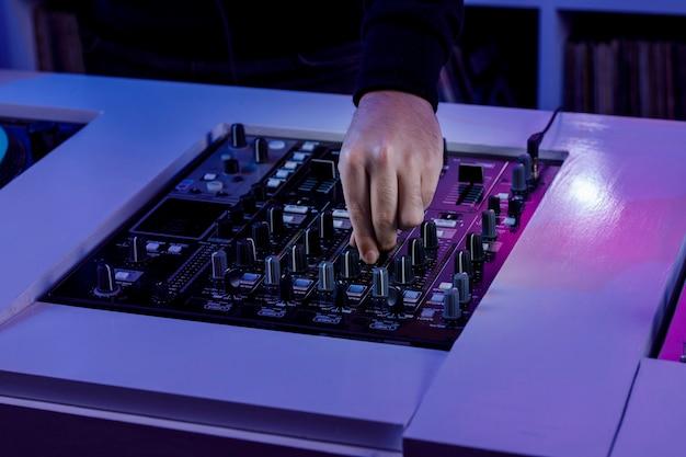 Mezcladora de audio de dj con tocadiscos de vinil en tienda de discos con una mano manipulandola