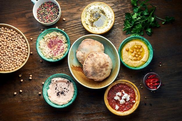 Мезе - восточный набор закусок, который подается в небольших пиалах с лавашем на деревянном столе. хумус, йогурт, мусс фета в мисках с хлебом. вид сверху