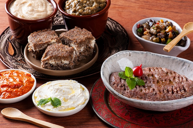Meze is an oriental set of appetizers served in small bowls with babaganoush, curd, hummus, muhammara and kibbeh