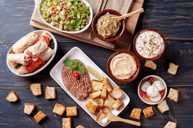 Meze is an oriental set of appetizers served in small bowls with babaganush, curd, hummus and kibbeh