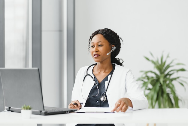Mhappy улыбающаяся афро-американская женщина-врач или медсестра с гарнитурой и ноутбуком, проводящая конференцию или видеозвонок в больнице