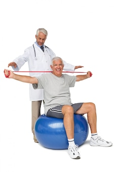 Mhysiotherapist looking at senior man sit on exercise ball with yoga belt