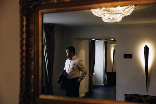 Miの窓の前に立っているタキシードの男の反射