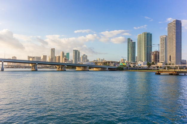 Miami city skyline panorama at blue sky cloudy and bridge over sea with reflection