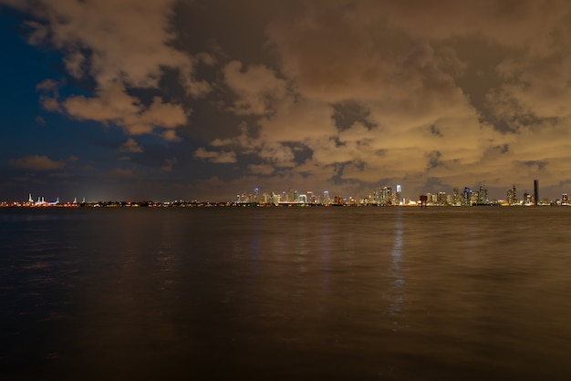 Miami, florida cityscape skyline on biscayne bay. panorama at dusk with urban skyscrapers and bridge over sea with reflection.
