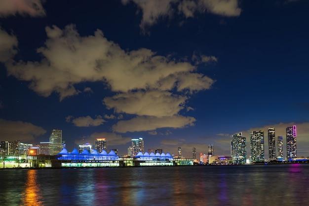 フロリダ州マイアミの夜のダウンタウン。反射のある海の上の都市の高層ビルとマイアミ市のスカイラインのパノラマ。