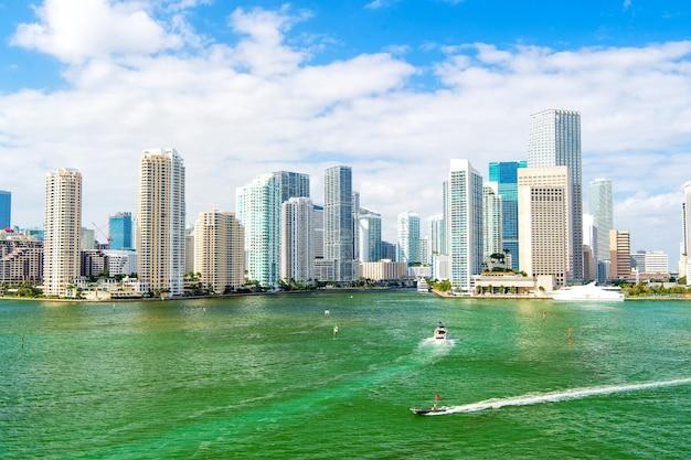 マイアミのスカイライン。ヨットは、米国マイアミの曇り青空に浮かぶ都市の高層ビルに向けて、海または海の水を航行します。夏休み、ワンダーラスト、旅行、コンセプト。