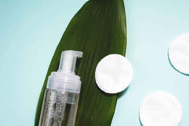 パステルブルーの表面にヤシの葉のミセル水と綿棒。メイク落としと洗い流しのコンセプト。自然なトナーで肌に潤いを