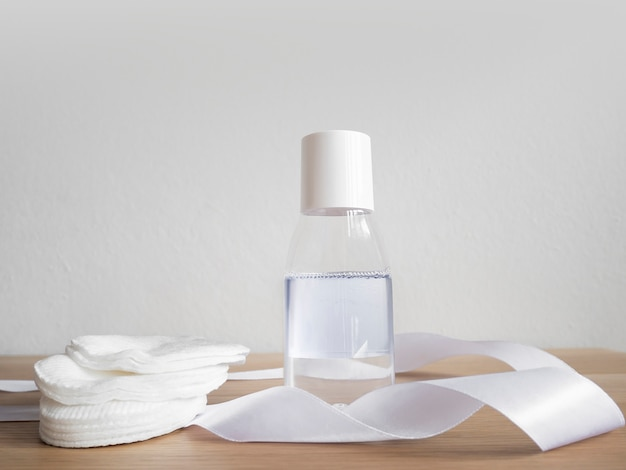 Micellar water with cotton pads on wooden table and white wall.