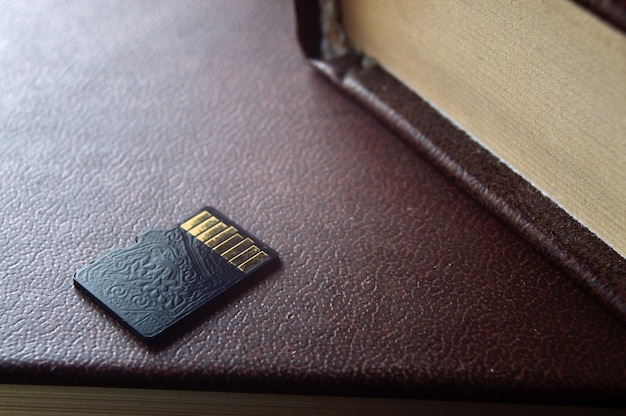 Micro sd card lies on top of a paper book, golden contacts at the top. close-up.