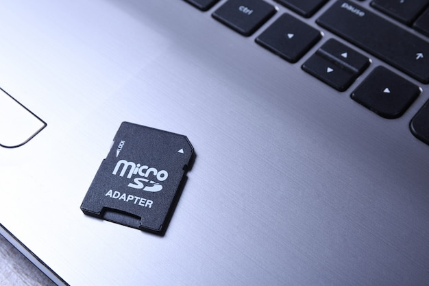 Micro sd memory card adapter on grey laptop keyboard on the wooden table. close up