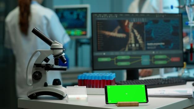 微生物学者が血液サンプルを現代の研究室に持ち込み、スマートフォンの近くに置いて、机の上に置かれた緑色のクロマキー画面を操作します。バックグラウンドで薬を開発しているバイオテクノロジー科学者のチーム
