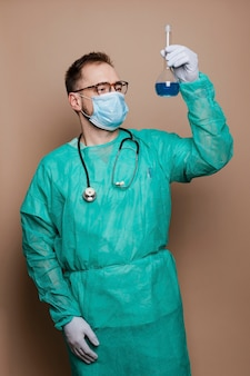 Microbiologist in a green gown holding a volumetric flask