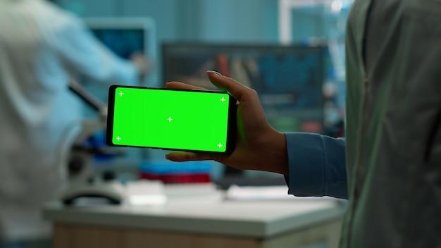 Микробиолог держит смартфон с зеленым дисплеем с цветным ключом перед камерой в современной лаборатории. команда ученых-биотехнологов разрабатывает лекарства с помощью планшета с макетом экрана.