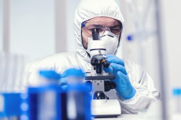 Исследователь микробиолога в ppe и защитных очках в медицинской лаборатории, смотрящей через микроскоп. ученый в защитном костюме сидит на рабочем месте с использованием современных медицинских технологий во время глобального