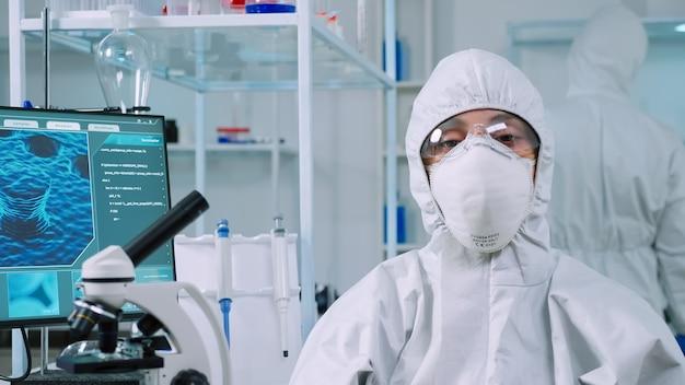 現代の設備の整った実験室でカメラを見ているppeスーツを着て実験室に座っている微生物学者。科学研究のためのハイテクおよび化学ツールを使用してウイルスの進化を調べる科学者のチーム