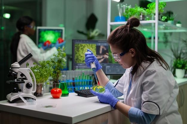 Microbiologist woman putting liquid in translucent petri dish using micropippete