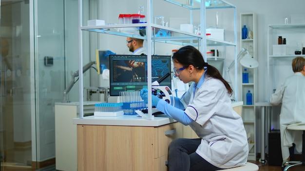현미경으로 샘플을 보고 있는 현대 실험실에서 새로운 백신을 위해 일하는 미생물학자. 과학 연구를 위한 첨단 화학 도구를 사용하여 바이러스 진화를 조사하는 다민족 팀.