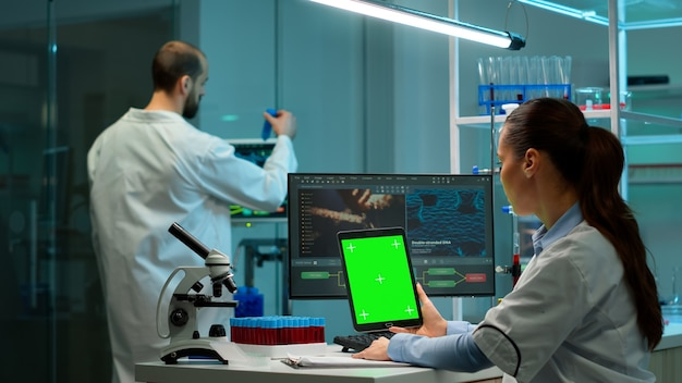 Microbiologist working on notepad with green chroma key display in modern equipped lab. team of biotechnology scientists developing drugs using tablet with mock up screen.