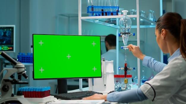 Ученый-микробиолог, печатающий на клавиатуре, работает с компьютером с зеленым экраном с клавишами цветности, разрабатывая вакцину, лекарства и антибиотики. высокотехнологичная лабораторная полка с пробирками, флаконами для таблеток, с образцами крови