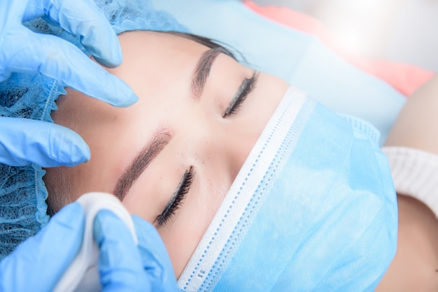 Microblading eyebrows workflow. permanent makeup for eyebrows having professional eyebrow tattoo in beauty salon.