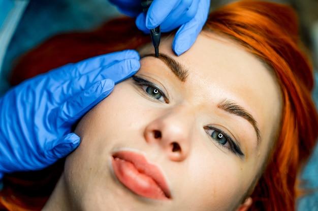 美容院での眉毛のマイクロブレード、マイクロピグメント。眉毛を染めた女性。眉毛のアートメイク。閉じる