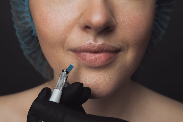Процесс микроблейдинга в салоне красоты. женщина, имеющая тонированные брови