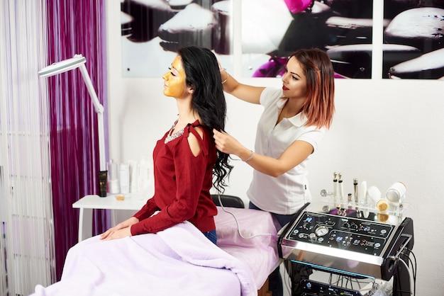 医師美容師は、美容サロンで顔にゴールドマスクを持つ美しい、若い女性の髪に手順microcurrent療法を行います。