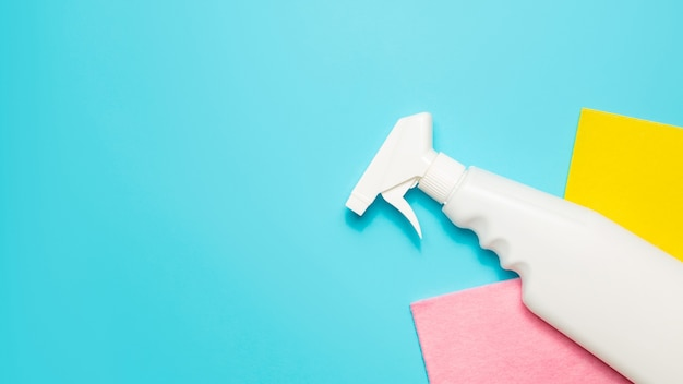 Microfiber cloth and spray cleaner on a blue background, top view, copy space. cleaning supplies.