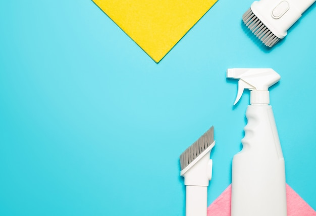 Microfiber cloth, vacuum cleaner attachments and spray cleaner on a blue background, top view, copy space. cleaning supplies.