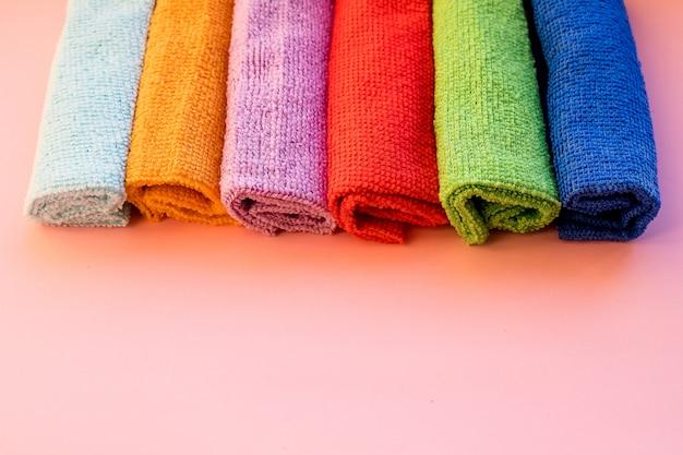 Полотенца из микрофибры, на розовом фоне. концепция бытовых услуг по уборке. копирование пространства