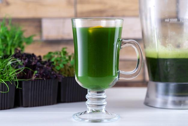 台所のテーブルの上のマイクログリーンジュース。ブレンダーのマイクログリーン。自宅でマイクログリーンのスムージーを作りましょう。健康的で有機的な食品