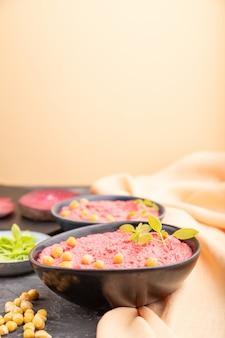 Хумус с ростками свеклы и базилика microgreen в керамическом шаре на предпосылке черного и oarange.