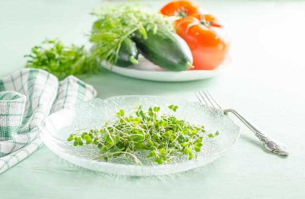 Микрозелень на тарелке с овощами на заднем плане, концепция здорового веганского сыроедения